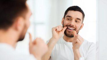 Man Flossing his teeth