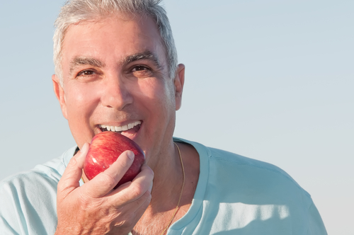 Man with denture eating apple